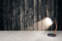 Small table lamp. Concrete surface and aged wooden wall with small, turned on table lamp. Mock up, 3D Renderin Royalty Free Stock Photo