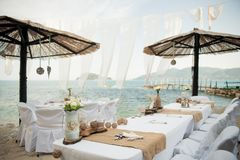 Small tables under parasols await the lucky guests of this intim. Stunning wedding stock photography from Zakynthos Greece! A stunning summer wedding reception Stock Photography