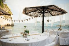 Small tables under parasols await the lucky guests of this intim. Stunning wedding stock photography from Zakynthos Greece! A stunning summer wedding reception Royalty Free Stock Photography