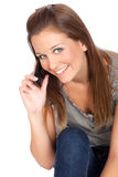 Small talk. Close up of a beautiful young woman talking on a mobile/cell phone, isolated on white Royalty Free Stock Images