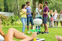 Small talk at grill party. Young people having small talk at grill party Stock Photography