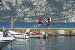 Small talk at the lake after biking - garda trentino italy. A girl and a boy get to know Stock Photo