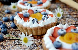 Small tart. Small basket shaped tart with peaches, strawberries and cream Royalty Free Stock Image