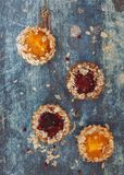 Delicious tarts with different fillings and almond. Small tarts with different fillings on rustic table. Top view, blank space stock images