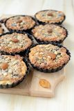 Small tarts with nut filling on a wooden board. Stock Photos