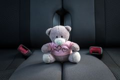 Small teddy bear not fastened sitting on a car seat royalty free stock photography