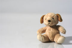 Small teddy bear sitting in a studio. Animal, baby, background, bear, child, cloth, eyes, gift, giving, grief, handmade, heart, isolated, love, plaything Royalty Free Stock Photos