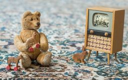 Small teddy bear watch cartoons in the television - scene with old toys. Small teddy bear plays with toys and watch tv like a real child - sits on a carpet stock image