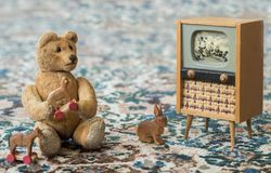 Small teddy bear watch cartoons in the television - scene with old toys. Small teddy bear plays with toys and watch tv like a real child - sits on a carpet stock photo