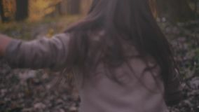 Small teenage girl with long brunette hair and stylish look. Scared little girl running in the forest, she looks around