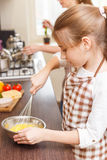 Small teenage girl whisks eggs in the mixing bowl Royalty Free Stock Photography