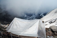 Small tent on a mountain side. In a morning with smoked clouds Royalty Free Stock Photos