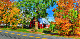 Small 18th century home surrounded by the beautiful colorful of VT fall foliage HDR. Stock Photo