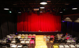 Small theatre hall with red curtains, stage and chairs. Small empty theatre hall with red curtains, stage and number of colorful chairs Royalty Free Stock Photography