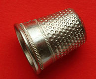 A small thimble. On a red surface Royalty Free Stock Photos