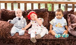 Small three children: black american, caucasian boys and russian baby girl siting Royalty Free Stock Photos