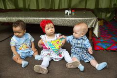 Small three children: black american, caucasian boys and russian baby girl siting up Royalty Free Stock Photography