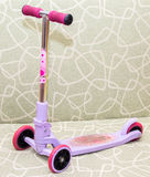 Small three-wheeled children pink scooter on couch Stock Photo