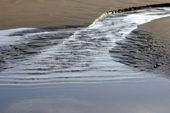 Small tidal flow on the beach. Blue and brown setting, reflections of the sky and clouds in the water Royalty Free Stock Photos