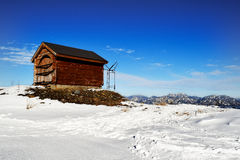 Small timber hut at the top of Hakuba Mountain range. A different mountain range can also be seen in the distance Stock Photo