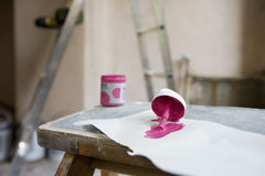Small tin of pink paint and paintbrush on paper in undecorated room, close-up, focus on foreground Stock Photography