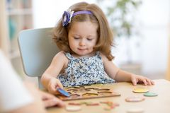 Small toddler or baby kid playing with puzzle shapes on low table in children room in nursery or preschool. Stock Photo