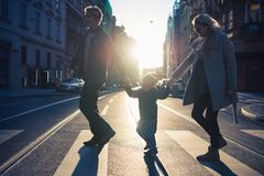 A small toddler boy with parents crossing a road outdoors in city at sunset. royalty free stock photo