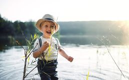 A small toddler boy standing by a lake at sunset. Copy space. A small toddler boy with a hat standing by a lake at sunset. Copy space royalty free stock image