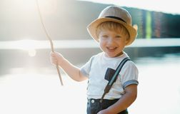 A small toddler boy standing by a lake at sunset. Copy space. A small toddler boy with a hat standing by a lake at sunset. Copy space stock photo