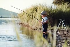 A small toddler boy standing by a lake at sunset, fishing. Copy space. Copy space stock images