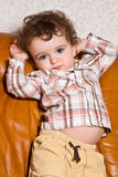 small toddler with on a leather brown sofa Royalty Free Stock Images