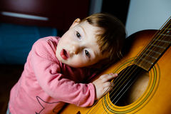Small toddler listening to sound of a guitar Royalty Free Stock Photography