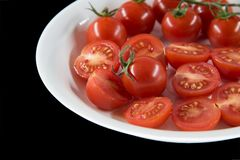 Small tomato on dish with black background royalty free stock photos