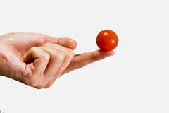 Small tomato on a female fingers Stock Images