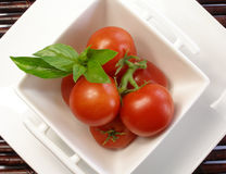 Small tomatoes with basil 2. Small tomatoes with basil in a chinaware square bowl stock photo
