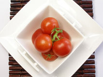 Small tomatoes in a chinaware. Square bowl stock image
