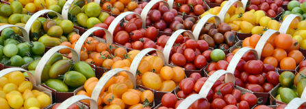 Small tomatoes. Heirloom small tomatoes on display at the farmers market Stock Photos