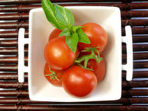 Small tomatoes with a leaf of basil. Small tomatoes with basil in a china bowl stock photography