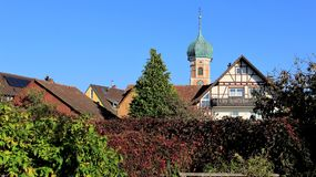 Small Topical Church And Local Houses. Small church topical local style with climber leaves and clear sky on sunny day in  Allensbach Germany Royalty Free Stock Image