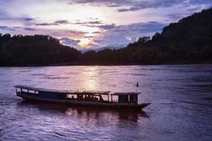 Small tour boat cruises along the Mekong river in Luang Prabang, Laos, during sunset. Small tour boat cruises along the Mekong river in Luang Prabang, Laos royalty free stock photography