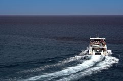 Small tourist boat. A view of a small boat fulled with tourists on a short day trip out to sea Stock Images