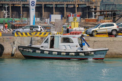 Small tourist boat at berth in Piombino seaport, Italy Stock Image
