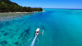 Small tourist boat sailing in turquoise Pacific ocean water Tahiti French Polynesia seascape in stunning 4k aerial view. Small tourist boat sailing in turquoise stock video