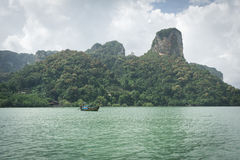 Small tourist boat in sea under mountain and cloudy sky Royalty Free Stock Photography