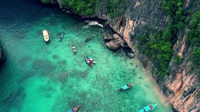 Small tourist boats in calm turquoise blue ocean water surrounded by big tropical stone rock mountain forest in 4k stock video