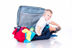Small tourist collects things in a suitcase for travel Royalty Free Stock Images