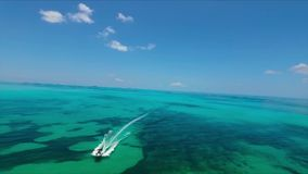 Small tourist motor boat sailing in turquoise blue deep reef ocean water in endless horizon seascape skyline of Florida. Tourist motor boat sailing in turquoise stock video