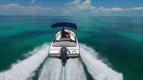 Small tourist motor boat sailing in turquoise deep blue reef ocean water in endless horizon skyline seascape of Florida stock footage