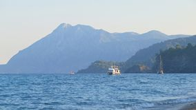 Small touristic boat floating along sea coast, surf waves, sunset, southern coast of Turkey. Mountains are in background stock footage