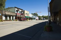 Small Town. Main street of Cedaredge, Colorado on a sunny day with a brilliant blue sky, showing the roadway, commerical buildings, and a vehicle. Cedarege is at Stock Photo